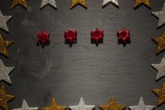 四个蜡烛盛开与在板岩的烟与星框架 免版税图库摄影