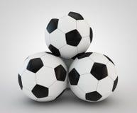 四个足球面对在白色的金字塔 库存图片