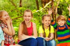 四个逗人喜爱的孩子获得乐趣在夏天森林 免版税库存图片