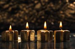 四个金黄出现蜡烛点燃有bokeh背景 免版税图库摄影