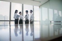 四个年轻商人支持的会议桌 免版税图库摄影