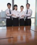 四个年轻商人支持的会议桌 库存照片
