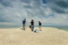 四位年轻摄影师在工作、海边和夏天 免版税图库摄影