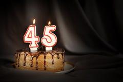 四十五年周年 生日与白色灼烧的蜡烛的巧克力蛋糕以第四十五的形式 免版税库存照片