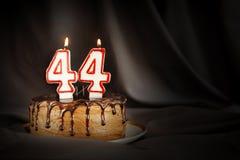 四十四年周年 生日与白色灼烧的蜡烛的巧克力蛋糕以第四十四的形式 免版税库存照片