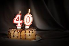 四十年周年 生日与白色灼烧的蜡烛的巧克力蛋糕以第四十的形式 免版税库存图片