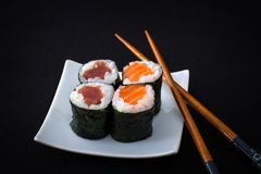 四双三文鱼、金枪鱼maki寿司和筷子在黑色 免版税库存图片