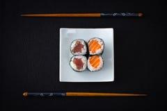 四双金枪鱼三文鱼maki寿司和筷子在黑色 图库摄影