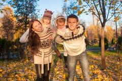 四口之家与两个孩子获得乐趣在秋天 图库摄影