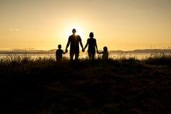 四口之家在日落由后照的阴影黑色 免版税库存图片