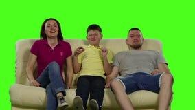 四口之家坐有微笑的长沙发 绿色屏幕 慢的行动 股票视频