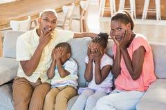 四口之家的画象观看的电视 免版税库存图片