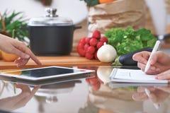 四只人的手特写镜头是姿势示意在一种片剂在厨房里 获得的朋友乐趣,当选择菜单或时 免版税库存照片