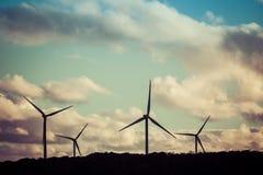 四台风轮机剪影在美好的日落的 库存照片