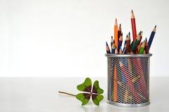 四叶三叶草和五颜六色的铅笔 库存照片
