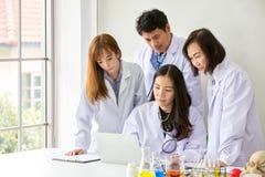 四名亚裔医护人员 亚裔医生画象  做在实验室里的化学家 有测试和研究的年轻科学家 免版税库存图片