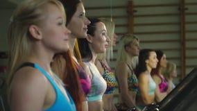 四名体育妇女在踏车,在镜子的反射走 慢动作射击 影视素材