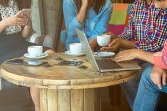 四名妇女通过分享从笔记本的信息和喝在咖啡店的咖啡做会议 免版税图库摄影