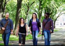 四名学生走 免版税库存照片