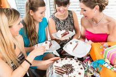 四名美丽的妇女和微笑的最好的朋友,当分享生日蛋糕时 免版税图库摄影