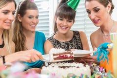四名美丽的妇女和微笑的最好的朋友,当分享生日蛋糕时 库存图片