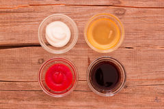四在杯子的不同调味汁在桌上 免版税库存图片