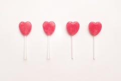 四在空的白皮书背景的桃红色华伦泰` s天心脏形状棒棒糖糖果 行家最小的爱概念 顶视图 图库摄影