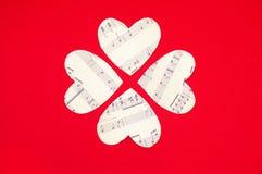 四在红色背景的纸心脏 库存照片