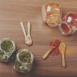 四块玻璃瓶子用香料和四木匙子在桌上 免版税库存照片