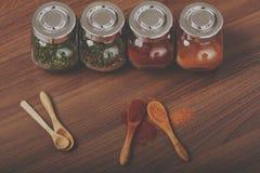 四块玻璃瓶子用香料和四木匙子在桌上 库存图片