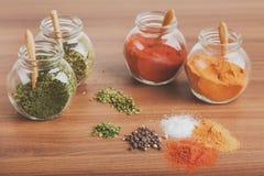 四块玻璃瓶子用香料和香料在木书桌上堆积 免版税库存图片