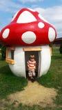 四岁男孩和伞菌房子在公园 免版税图库摄影