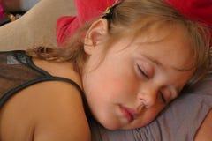 四岁的女孩在她的mother& x27睡觉;s身体 库存图片