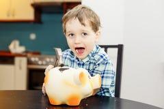 四岁的男孩捣毁的猪存钱罐 库存图片