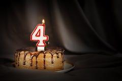 四年周年 生日与白色灼烧的蜡烛的巧克力蛋糕以第四的形式 免版税库存图片
