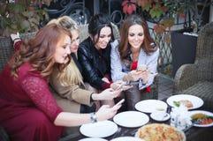 四年轻美女拍摄在一个咖啡馆的食物与电话 免版税库存照片