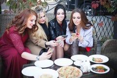 四年轻美女拍摄在一个咖啡馆的食物与电话 库存图片