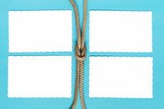 四张纸片与一条绳索的在蓝色背景 图库摄影