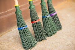四把新的笤帚由绿色塑料制成 库存图片