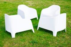 四把现代白色塑料椅子在绿草站立 图库摄影