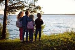 四支持湖的逗人喜爱的矮小的兄弟姐妹享受美好的日落视图 探索自然的孩子 免版税库存照片