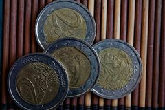 四枚欧洲硬币在木竹桌衡量单位说谎是两欧元 免版税库存图片