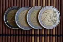 四枚欧洲硬币在木竹桌连续衡量单位说谎是2欧元 免版税库存图片
