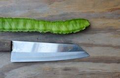 四棱豆和厨刀在木板 库存照片