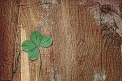四片叶子好运的三叶草三叶草在老木板条背景  温暖的口气 免版税图库摄影