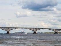 四甲板客船通过在路桥梁下 俄罗斯,城市萨拉托夫 免版税库存图片