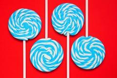 四白色和在红色背景的蓝色棒棒糖 免版税库存图片