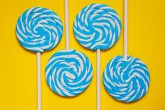 四白色和在黄色背景的蓝色棒棒糖 免版税图库摄影