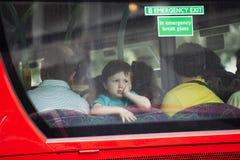 四看看的男孩公共汽车的后窗 免版税库存照片
