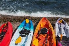 四艘多彩多姿的皮船在海滩站立,在小小卵石,海视图,夏天 免版税图库摄影